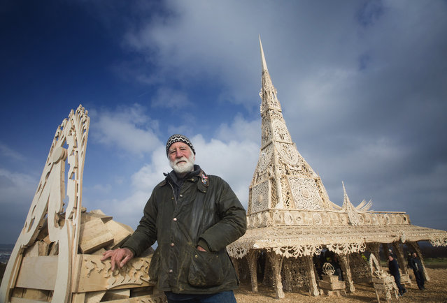 In this photo taken on Saturday, March 14, 2015, U.S. sculptor David Best poses for a photograph next to his 72-foot-tall (22-meter-tall) hand crafted wooden tower that overlooks Londonderry, Northern Ireland. More than 5,000 people a day have been visiting a hand-crafted wooden tower designed by Best. The structure, reminiscent of a Buddhist temple or an arabesque palace, was burned to the ground on Saturday night in front of 15,000 ticket-holders. (Photo by Brian Morrison/AP Photo)