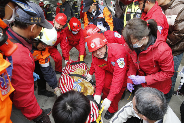 Rescue workers remove a victim from a collapsed building from an early morning earthquake in Tainan, Taiwan, Saturday, February 6, 2016. (Photo by Wally Santana/AP Photo)