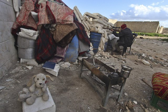 A rebel fighter takes position as he aims his weapon behind piled cement blocks at Sheikh Najjar frontline against forces loyal to Syria's President Bashar al-Assad in Aleppo February 4, 2015. (Photo by Hosam Katan/Reuters)