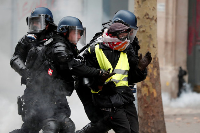 "French gendarmes apprehend a protester during clashes at a demonstration by the ""yellow vests"" movement in Paris, France, December 8, 2018. (Photo by Benoit Tessier/Reuters)"