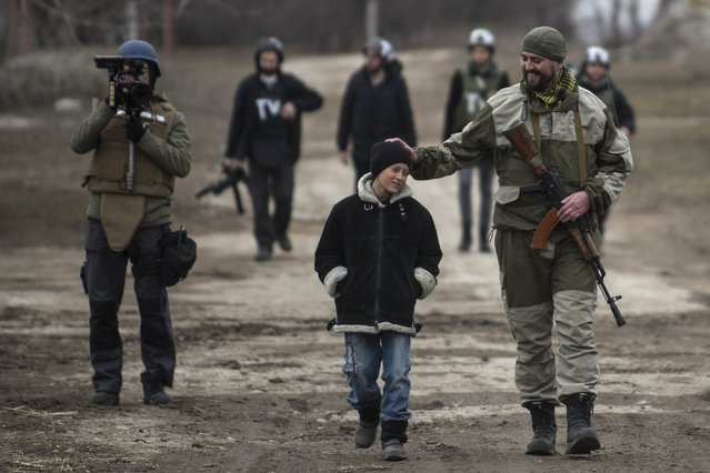 In this Thursday, February 26, 2015 file photo a Ukrainian serviceman speaks with a schoolboy in the village of Chermalyk, eastern Ukraine. (Photo by Evgeniy Maloletka/AP Photo)