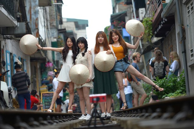 This photo taken on October 20, 2018 shows tourists posing for a photo on a middle of a railway track passing through an old residential district in central Hanoi. (Photo by Nhac Nguyen/AFP Photo)