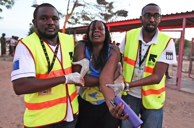 Paramedics help a student who was injured during an attack by Somalia's Al-Qaeda-linked Shebab gunmen on the Moi University campus in Garissa on April 2, 2015. (Photo by Carl De Souza/AFP Photo)