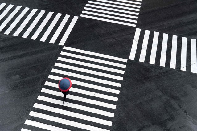 A pedestrian crosses an intersection on a rainy day in Tokyo on May 13, 2021. (Photo by Charly Triballeau/AFP Photo)