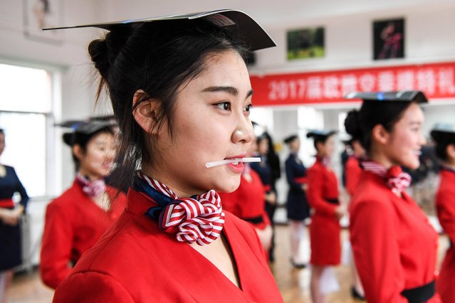 Students attend a stewardess skill training for the upcoming 2017 entrance examination for art majors in colleges in Luoyang, central China's Henan Province, January 4, 2017. Smiling training is also touched on in the classes as the fledgling flight attendants grasp a straw between their teeth. (Photo by Li Bo/Xinhua/Barcroft Images)