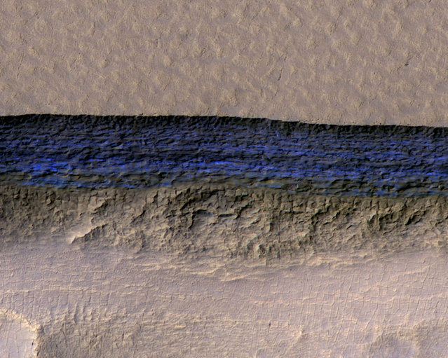 A cross-section of a thick sheet of underground ice is exposed at the steep slope that appears bright blue in this enhanced-color view of Mars from the High Resolution Imaging Science Experiment (HiRISE) camera on NASA's Mars Reconnaissance Orbiter in this image released on January 11, 2018. (Photo by NASA/JPL-Caltech/UA/USGS/Handout via Reuters)