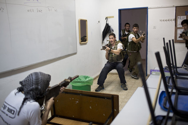 In this Tuesday, March 24, 2015 photo, Israeli high-school seniors preparing to join the Israeli military participate in an urban fighting drill as part of privately run military combat fitness training, in Kibbutz Mizra, northern Israel. (Photo by Oded Balilty/AP Photo)
