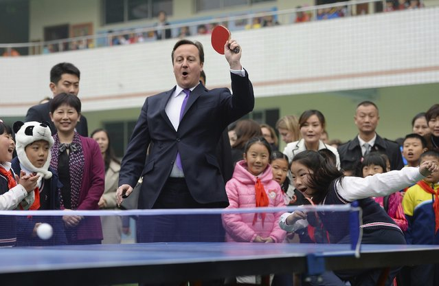 British Prime Minister David Cameron plays table tennis with primary school students during his trip to Chengdu, Sichuan province, December 4, 2013. (Photo by Reuters/China Daily)