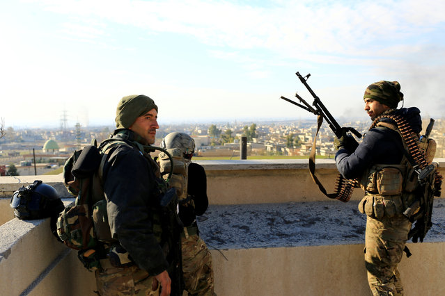 Iraqi rapid response forces stand on the roof of a building during a battle with Islamic State militants in the Mithaq district of eastern Mosul, Iraq, January 3, 2017. (Photo by Thaier Al-Sudani/Reuters)