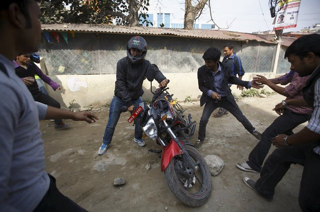 A man tries to save his motorcycle after protesters set it on fire during a nationwide strike, organised by the opposition alliance led by the Unified Communist Party of Nepal (Maoist) to demand the new constitution be drafted with the consensus of all political parties, in Kathmandu April 7, 2015. (Photo by Navesh Chitrakar/Reuters)