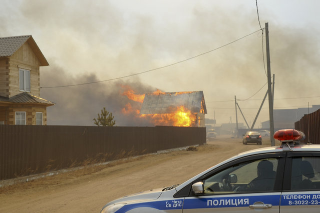 Police officers block a road to the burning village of Smolenka near Chita on Monday, April 13, 2015. (Photo by Evgeny Yepanchintsev/AP Photo)