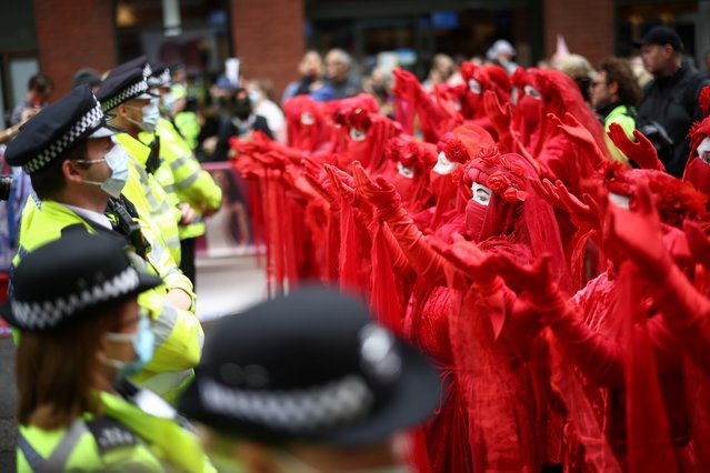 Extinction Rebellion Red Rebel Brigade activists perform as police officers stand guard during a protest, in London, Britain on August 23, 2021. (Photo by Henry Nicholls/Reuters)