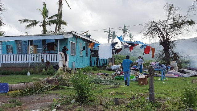 A family stands outside their damaged home after Cyclone Winston swept through Ba on the northern side Fiji's Viti Levu Island, February 22, 2016. (Photo by Jay Dayal/Reuters)