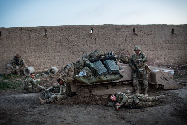 Soldiers with the United States Army's 3rd Battalion, 41st Infantry Regiment, collapse at the end of the day, during a two-day joint mission with the Afghan National Civil Order Police, near Command Outpost Siah Choy on March 25, 2013 in Kandahar Province, Zhari District, Afghanistan. (Photo by Andrew Burton/Getty Images)