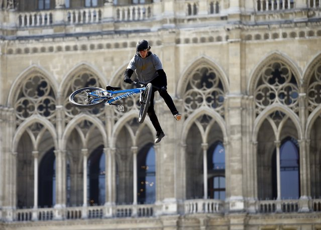 A biker performs a jump during a bike festival in front of the city hall in Vienna, April 11, 2015. (Photo by Leonhard Foeger/Reuters)