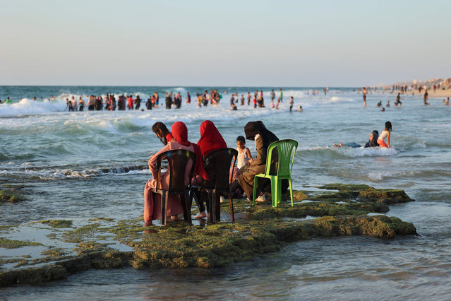 Palestinian women sit together at the beach of Deir al-Balah in central Gaza Strip on August 12, 2021. (Photo by Mohammed Abed/AFP Photo)
