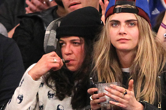 1/7/2014 - Detroit Pistons vs. New York Knicks at Madison Square Garden - Actress Michelle Rodriguez smoking what looks like an e cigarette or small pipe, sitting in the front row next to model Cara Delevingne during the 4th quarter. The two were hugging and touching each other and Rodriguez appeared to be very intoxicated.
