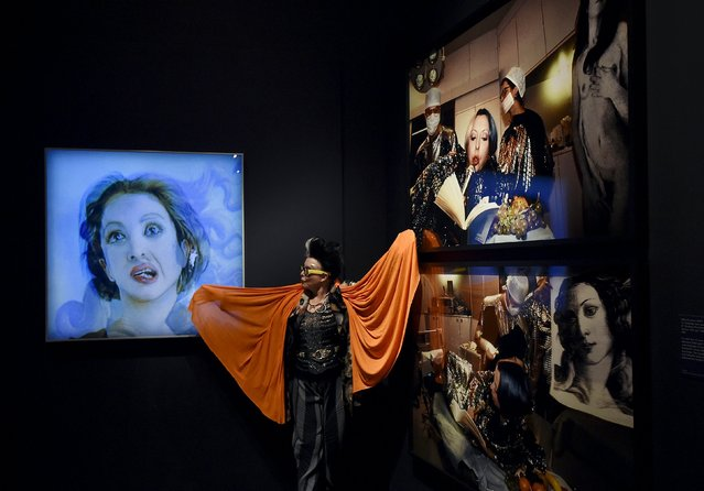 """French artist """"ORLAN"""" poses next to photographic portraits of herself at the Victoria and Albert museum in London, Britain, March 2, 2016. She underwent cosmetic surgery to resemble Botticelli's Venus and her photographic documentation of this procedure forms part of """"Botticelli Reimagined"""", an exhibition exploring the ways artists have responded to the artistic legacy of the fifteenth century artist Sandro Botticelli. (Photo by Toby Melville/Reuters)"""