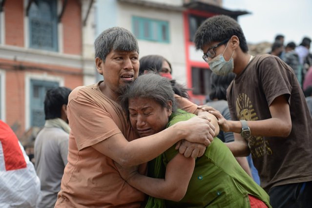 A Nepalese man and woman hold each other in Kathmandu's Durbar Square, a UNESCO World Heritage Site that was severely damaged by an earthquake on April 25, 2015. (Photo by Prakash Mathema/AFP Photo)