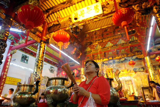 A woman prays in a temple during the Chinese Lunar New Year's festival in Chinatown, in Yangon, Myanmar January 27, 2017. (Photo by Soe Zeya Tun/Reuters)