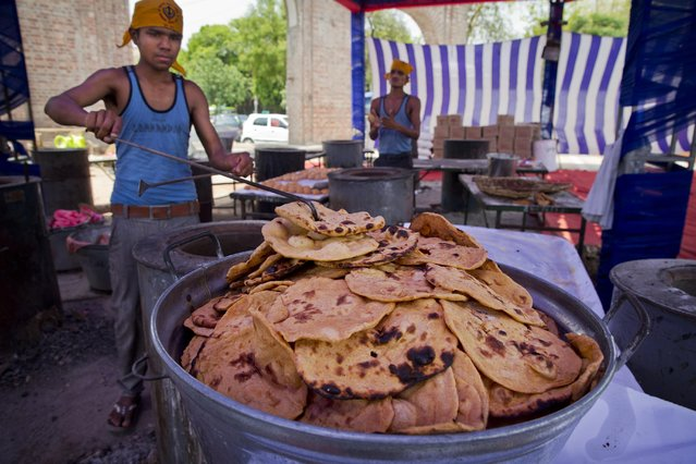 Workers prepare rotis, a type of Indian bread at the Bangla Sahib Sikh temple to be shipped as relief material to Nepal in New Delhi, India, Wednesday, April 29, 2015. The first aid shipments reached a hilly district near the epicenter of Nepal's earthquake, a U.N. food agency official said, and distribution of food and medicine would start Wednesday, five days after the quake struck. (Photo by Saurabh Das/AP Photo)