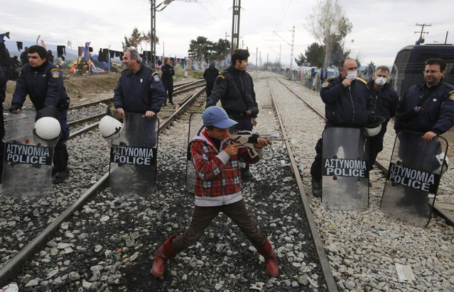 A boy plays with a toy gun in front of the policemen as other migrants block the railway track at the Greek-Macedonian border, near the village of Idomeni, Greece March 12, 2016. (Photo by Stoyan Nenov/Reuters)