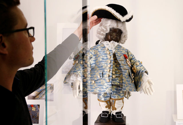 An employee adjusts a French outfit, a gift of King Louis XV in 1747, for the famous Belgian statue Manneken Pis at the museum called GardeRobe MannekenPis in central Brussels, Belgium February 2, 2017. (Photo by Francois Lenoir/Reuters)