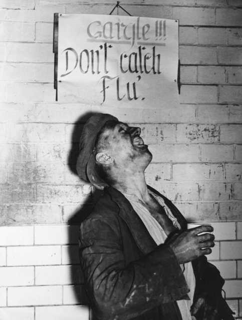 A miner at the Houghton Main Colliery, Yorkshire, England, has an anti-flu gargle after work, in front of a notice that advises him to do so, to avoid the serious epidemic that has effected miners at many neighbouring collieries, circa 1937. (Photo by Fox Photos/Getty Images)