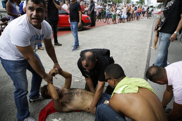 Civil Police officers detain a looter, who was shot in the leg by police when he tried to plunder an electronic store, in Vitoria, Espirito Santo state, Brazil, Monday, February 6, 2017. Protests by the friends and family of military police in Espirito Santo have led to an increase in crime and forced the shut-down of some state services, authorities said Monday. (Photo by Diego Herculano/AP Photo)