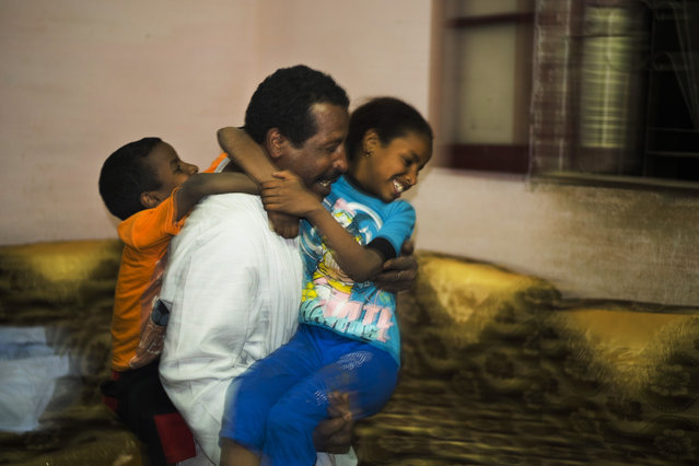 In this Friday, April 17, 2015 photo, Salama Osman, a migrant worker in Cairo, plays with his children Sameh, 5 1/2, left, and Zainab, 10, during a biannual trip back home in Abu al-Nasr, about 770 kilometers (480 miles) south of Cairo. Osman, 46, is on one of his two trips a year back home where he can relax with his family, a rare respite from his hectic job back in the always-bustling Egyptian capital. (Photo by Hiro Komae/AP Photo)