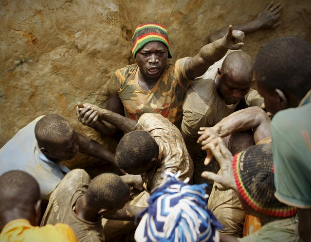 Prospectors quarrel as they search for gold at a gold mine near the village of Gamina, in western Ivory Coast, March 17, 2015. (Photo by Luc Gnago/Reuters)