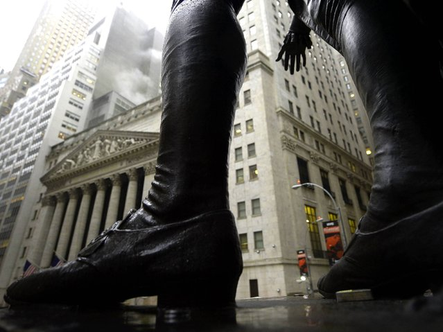 Rain falls with the New York Stock Exchange in the background as seen through the statue of George Washington at Federal Hall in Manhattan, on February 19, 2014. (Photo by Timothy Clary/AFP Photo)