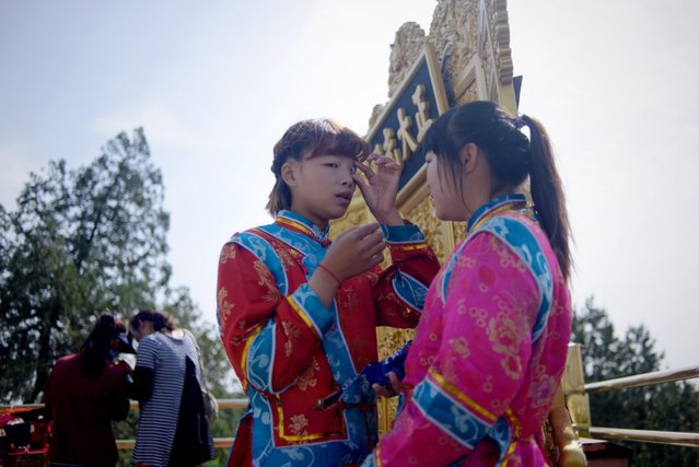 Two vendors wearing Qing dynasty clothing wait for visitors to take photos at a park near the Forbidden City in Beijing on May 3, 2015. (Photo by Wang Zhao/AFP Photo)