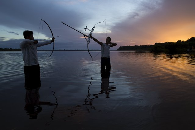 Kambeba Indian, Dream Braga (R), 18, and his friend Nelson Varge da Silva, pose for pictures at sunset on the banks of the Negro river at the village Tres Unidos, Amazon state May 9, 2015. (Photo by Bruno Kelly/Reuters)