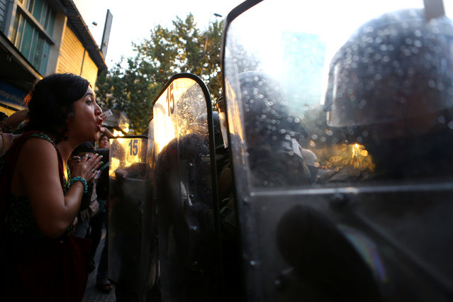 A woman argues with riot policemen during a rally marking the anniversary of the death of union leader Juan Pablo Jimenez, in Santiago, Chile February 21, 2017. (Photo by Ivan Alvarado/Reuters)