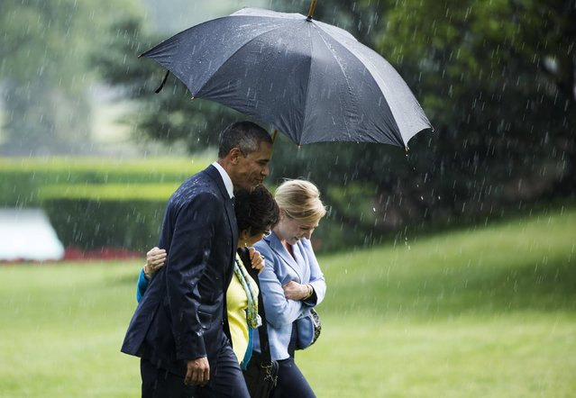 U.S. President Barack Obama holds an umbrella for Senior Advisor Valerie Jarrett (C) and Deputy Chief of Staff Anita Breckenridge (R) as they step from Marine One during a rain shower on the South Lawn of the White House in Washington May 18, 2015. (Photo by Joshua Roberts/Reuters)