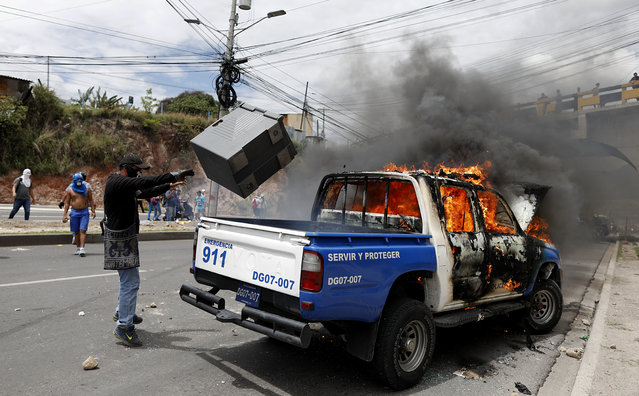 A man throws a bin at a torched police vehicle during a protest against the government of Honduras' President Juan Orlando Hernandez, in Tegucigalpa, Honduras, Thursday, May 30, 2019. Thousands of doctors and teachers have been marching through the streets of Honduras' capital for the last three weeks against presidential decrees they say would lead to massive public sector layoffs. (Photo by Elmer Martinez/AP Photo)