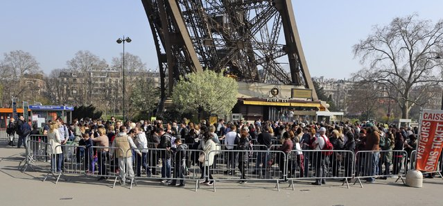 Tourists wait in line at the foot of the Eiffel Tower in Paris, Thursday March 13, 2014. Lines stretch for hours, leaving visitors to bake in the summer or soak in the rain for fear of losing their place. Socialist candidate for Paris mayor Anne Hidalgo wants to create an underground welcome area and rethink how people visit France's most popular monument. (Photo by AP Photo/Remy de la Mauviniere)