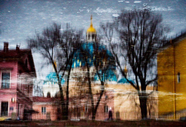 Buildings and the Trinity Cathedral are reflected in the Fontanka River in Saint Petersburg on December 5, 2018. (Photo by Olga Maltseva/AFP Photo)