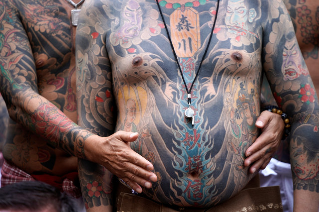 Participants pose showing traditional Japanese tattoos during the annual Sanja Matsuri festival in Tokyo's Asakusa district, Japan, 19 May 2019. Around two million people gathered in Asakusa streets during the three-day spring festival, one of Japan's biggest festivals. (Photo by Franck Robichon/EPA/EFE)