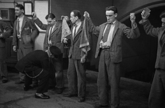 """A prison officer frisking prisoners during the """"rub-down"""" at Strangeways Prison in Manchester, UK on November 1948. (Photo by Bert Hardy/Picture Post/Hulton Archive/Getty Images)"""