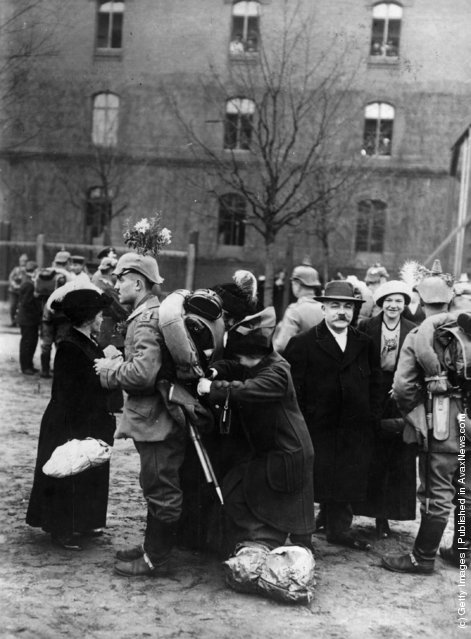 1914: A soldier with flowers on his helmet and equipment on his back prepares for departure during the mobilization of German forces