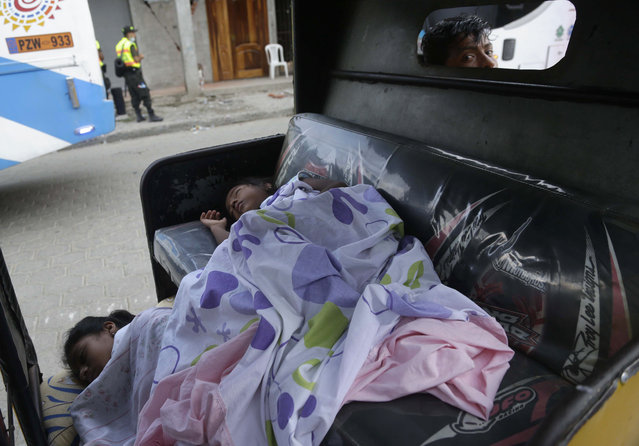 Girls sleep in the back of their father's moto-taxi as he watches them from the front seat, days after an earthquake in Pedernales, Ecuador, Wednesday, April 20, 2016. A fresh tremor rattled Ecuador before dawn Wednesday, a magnitude-6.1 jolt that set babies crying and shaken residents pouring once again into the streets, fearful of yet more damage following a monster earthquake over the weekend. (Photo by Dolores Ochoa/AP Photo)