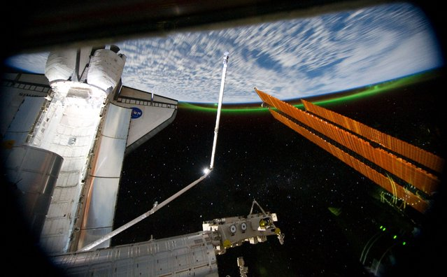 A panoramic view, photographed from the International Space Station, looking past the docked space shuttle Atlantis' cargo bay and part of the station including a solar array panel toward Earth, July 14, 2011. (Photo by NASA)
