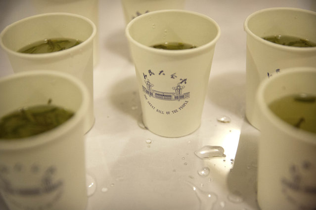 In this Friday, March 10, 2017 photo, cups of green tea bearing an image of the Great Hall of the People are available for delegates and visitors during a plenary session of the Chinese People's Political Consultative Congress (CPPCC) in Beijing. (Photo by Mark Schiefelbein/AP Photo)
