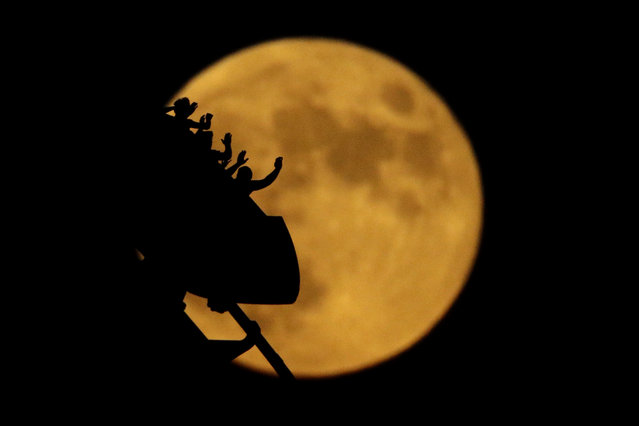 The full moon rises silhouetting roller coaster riders at the Worlds of Fun amusement park on the 50th anniversary of the Apollo 11 moon launch Tuesday, July 16, 2019, in Kansas City, Mo. (Photo by Charlie Riedel/AP Photo)