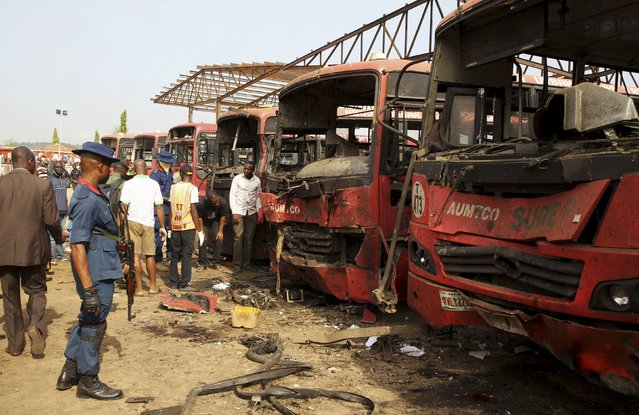Bomb experts search for evidences in front of buses at a bomb blast scene at Nyanyan in Abuja April 14, 2014. (Photo by Afolabi Sotunde/Reuters)