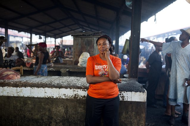 A woman stands next to a fishmonger stand after a massive fire at a market in Port-au-Prince, Haiti, Monday March 20, 2017. (Photo by Dieu Nalio Chery/AP Photo)