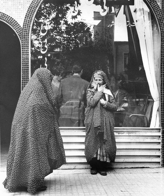1955:  Iranian women wait outside whilst the men meet in a teashop in Mashad, Iran