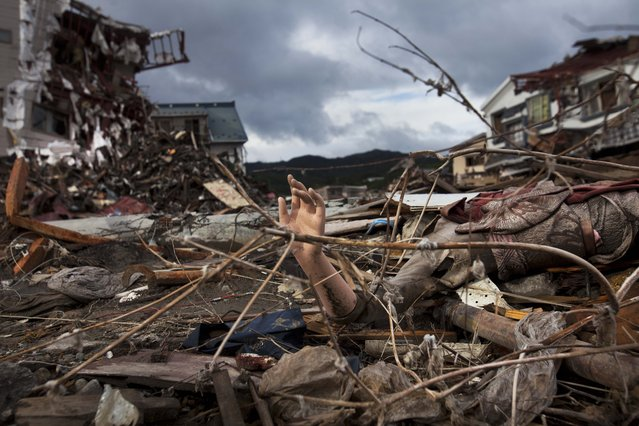 The arm of a mannequin sticks out from the rubble in a devastated neighborhood in Kesennuma, Miyagi prefecture, in northeastern Japan, Monday, May 30, 2011 which was destroyed in the March 11 earthquake and tsunami. (Photo by David Guttenfelder/AP Photo)